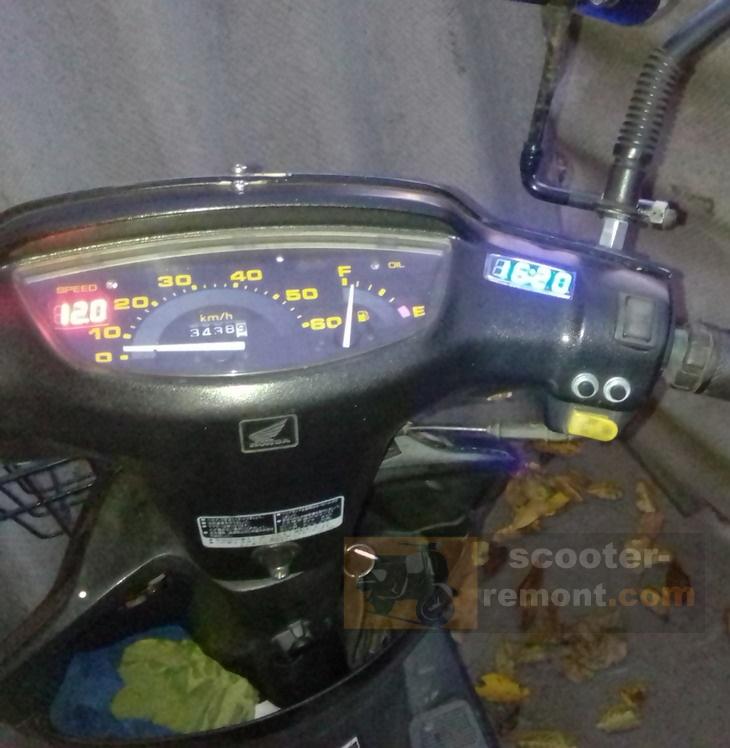 Часы возле приборной панели скутера